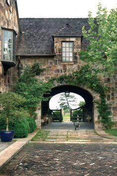 Motor court with a beautiful stone porte cochere and wood gate