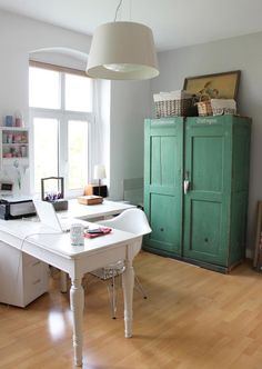 I really like these corner desks but more so I love the color of that cabinet!