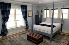 Nautical-themed bedroom with four-poster bed, blue stripped curtains and chest.