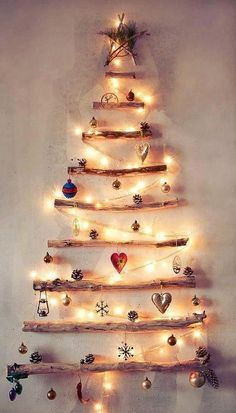 If you don't have a living room, or don't have the space to set up a life-size fir tree, create a 2-D tree on one wall of your studio apartment! This beautiful tree was created with 9 small logs attached to the wall, 1 string of white lights, several twigs + fir stems shaped into a star, and an assortment of ornaments hung from each branch! It can work above a fireplace, on the back of a door, or anywhere you have at least 2-3 feet width of wall space to use!