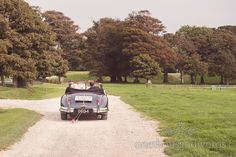 Classic Jaguar wedding car with just married sign leaves Lulworth Castle wedding. Photography by one thousand words wedding photographers