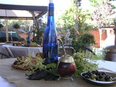 A typical Argentine table.  Use a wine bottle as your candle holder, surround it with green leaves from the garden.  Add the Argentine gourd called mate used to drink yerba mate.