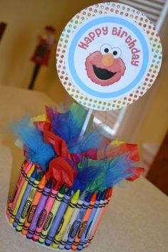 Elmo centerpiece made using crayons, tissue paper, and tulle.  See more Elmo birthday party ideas at www.one-stop-party-ideas.com