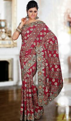 Heavily Embroidered Maroon Crepe Sari Weave your way into any party with this, pinkish maroon faux crepe sari. Saree features embroidered and sequins enhanced floral motifs and decorative patterns all over. Beads, sequins enhanced contrast floral patterned border makes it an eye catching ensemble. Comes with a matching stitched round neck blouse with 6 inches sleeves.  #HeavilyEmbroideredSaree #IndianWeddingSarees