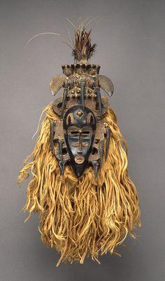 Africa   Face Mask (Kpeliye'e), 19th–mid-20th century   Côte d'Ivoire; Senufo   Wood, horns, raffia fiber, cotton cloth, feather, metal, sacrificial material