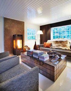 Eierne ønsket følelsen av å sjekke inn på hotell når de kom på hytta. Det har de lykkes i, med dette fantastiske interiøret. I stuen dominerer favorittfargen brunt i flere nyanser. Sofaen og lenestolene i grovvevd ull er fra Moroso og gir en maskulin tyngde til det lyse rommet. Sofabordet er egendesignet og er laget hos en lokal murer i glaserte kakler fra Fired Earth. Lampene er av Philippe Starck og vedovnen er av merket Titan. Gardinene i tykk velur er sydd etter mål. Philippe Starck, Lily, Homes