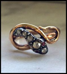 An antique 18 karat yellow gold and silver snake ring with rose cut diamonds and ruby eyes. Circa 1700's.