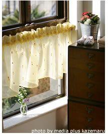黄色いレースのカーテンにビーズをとりつけたハンドメイドのカフェカーテン。太陽の日があたるとキラキラして、華やかな気分を演出できます。