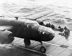 DOLITTLE'S 4.18.42 TOKYO RAID: With flight deck personnel dropping to the deck to avoid its turning propellers, A north American B-25B Mitchell medium bomber starts its takeoff roll aboard USS Hornet (CV-8), 18 April 1942. (U.S. Navy)