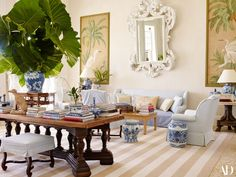 The living-room furniture, including a Punta Cana sofa by Bunny Williams Home, wears slipcovers of blue Duralee cotton. Chinoiserie panels flank a carved wood mirror from Harrison & Gil, painted white.