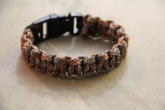 Paracord Survival Bracelet with Clip Orange Black by CordNinja. Paracord Survival Bracelet with Clip - Orange, Black, and Grey Pattern.