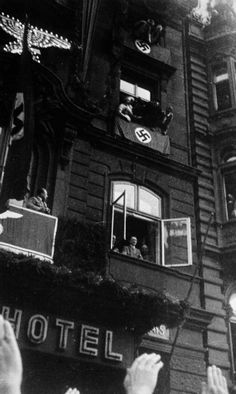 Hitler acknowledges the cheers of the crowd from the balcony of the Dom Hotel in Cologne after the reoccupation of the Rhineland, 7 March 1936.