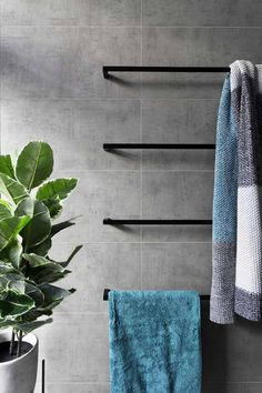 this modern grey and white bathroom, matte black accents like towel bars add a sophistication to the bathroom, while the touches of blue in the towels and green in the plant add a pop of color to the otherwise neutral space. Gray And White Bathroom, Grey Bathrooms, Modern Bathroom, Beige Bathroom, Small Bathroom, Silver Bathroom, Hang Towels In Bathroom, Bathroom Towel Hanger, Bathroom Caddy