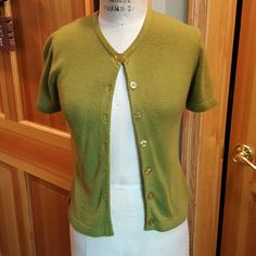 Olive green cardigan sweater This is a great little sweater to wear over any camisole. Very light piling in some spots, cute cut out designs on lower part of both sides. Very good condition. Takeout Sweaters Cardigans