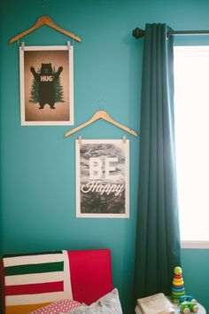 Love the idea of hanging art from vintage clothing hangers.
