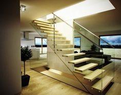 un escalier avec des marches blanches et des garde-corps en verre