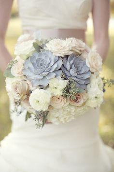 bouquet of amnesia roses, blush spray roses, silver brunia, pale green and purple succulents, fresh lavender, queen anne's lace, and grey dusty miller wrapped in grey ribbon with the stems showing.