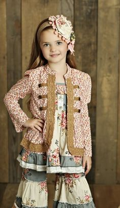 Our Mustard Pie Sugar Blossom London Jacket for girls from Adorables Children can be dressed up with a pretty dress or paired with fun leggings from Mustard Pie's Sugar Blossom collection. This military-style long-sleeved lightweight jacket is in a bright floral pattern with beautifully crocheted lace trim that lines the front and jacket hem of this no-collar jacket in sizes for infants, toddlers and growing girls. The open-front jacket has a button front and long sleeves that flare sligh...