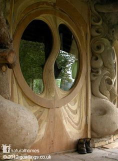 This beautiful door, with sculpted cob walls, looks out over the banks of a small stream in Somerset, England where the local dialect still has remnants of the Anglo-Saxon language. You can see more pictures of this home at www.naturalhomes.org/goatlings.htm