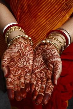 The Indian bride's hands are decorated with mehndi on the day of her marriage when she leaves her parents' home and goes with her husband to start a new life. The color red is the color of marriage in India.