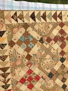 Auction quilt from first half of the 19th century; large-scale chintz plus plaid and stripes. Subtle use of color to highlight corner patches.