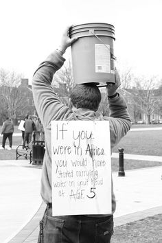 """JT Noland, WE LEAD Social Justice Issue Team Leader, carries water on his head in solidarity with millions of women worldwide during """"Be Hope to Her,"""" part of Social Justice Awareness Week 2013."""