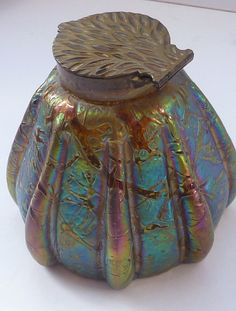 This is a museum quality antique glass inkwell. It is made by Kralik glass and has a stunning iridescent sheen with shimmering rainbow colours,