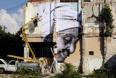 Havana, Cuba: Men put up artwork by Cuban-American artist José Parlá and French artist JR on a building in Havana for the upcoming 11th Havana Biennial contemporary art exhibition
