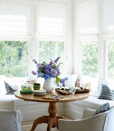 The homeowner of this California farmhouse pulled up a pine pedestal table and slipcovered armchairs to built-in benches.