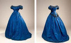 Balkjole med langt slæb. Kjolen er syet i blåt silketaft og har pynt af sorte maskinkniplinger.