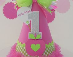 **SEE SHOP HEADER FOR CURRENT TURN TIME**  Lemonade and sunshine! So sunny and bright for your little sunshine girl! Yellow chevron cardstock hat. Candy pink cardstock trim. Adorned with pink trim and ruffled ribbon on the base. All seams are trimmed. Topped with an adorable layered bow with boa pom. Number of choice: Candy pink and light yellow (layered). Jeweled personalized balloon and string. Balloon can read Birthday Girl, Sunshine Girl or you can add your childs name. A jeweled layered…