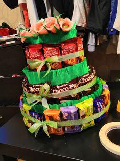 нижний ярус состоит из конфет птичье молоко разных вкусов. Второй - чоко пай. и третий  из шоколадных вафель. Верх украшен цветами из гофры, в серединке трюфельные конфетки или чупа чупсы. Основание торта -картон. отделка гофрированной бумагой желтого и зеленого цветов.
