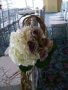 Curly willow loops over the chair and accented with hydrangea and roses.