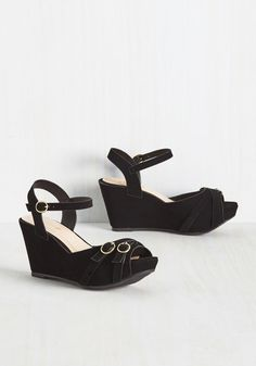 Make your ensemble look totally bold in a snap by slipping your toes into these black platform wedges! This vegan faux-suede pair boasts a crisscrossing straps at the peep toes and shiny gold buckles that turn heads everywhere they tread.