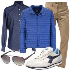 Outfit composto da pantaloni light knaki a vita normale, camicia blu fantasia a quadri, piumino blu in nylon, sneakers bianche e blu e occhiali da sole polarizzati.