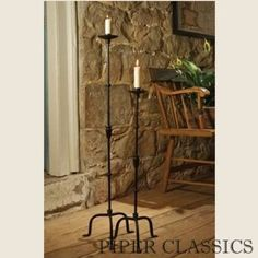 """We fell in love with these floor-standing, wrought ironcandlesticks because of their interesting details, primitive blackfinish and super price! If you're looking for something unique to fill a corner, sit by the fireplace or add interest to an otherwise boring space these are perfect! Sold as a set of 2 -26"""" and 36"""" high with 9"""" bases. Holds a standard taper candle."""