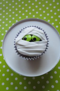 Mummy Cupcake with Green Eyes | These sweet and spooky treats are going to be a hit. If you're looking for a little dessert inspiration for your Halloween party or school party these mummy cupcakes are just what you've been searching for. If your vision of a Halloween mummy is more scary than sweet, we're here to change your perception with our Halloween mummy cupcakes. From a pudgy (and cute) mummy to a fondant-wrapped mummy with green eyes, these mummy recipes are sure to please this