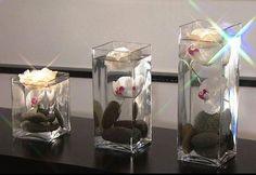 Garrafas de vidro decoradas com  pedras de rio flores e vela