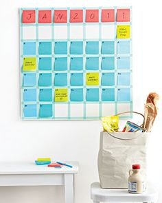 Instead of crossing out plans as dates shift, just move the notes and stack them up on busy days. Start with a 26 1/2-inch square sheet of Masonite fiberboard. Spray-paint it white, and let dry. Then use tape to create a seven-by-seven grid of three-inch squares.