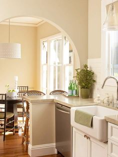 Custom LookCustom Look  A broad archway preserves the coziness of the original breakfast room while allowing guests to converse with the cook. In addition to sporting fresh functionality, the kitchen's look received an upgrade that combines classic cottage style with chunky steel hardware and straightedge countertops in limestone and butcher block.    arch?