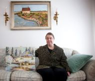 Peggy Tyler sits for a portrait photo with two of her paintings in her home in Roy. Tyler has Down syndrome and Crohn's disease but doesn't ...