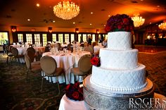 Embossed wedding cake with red rose bouquet. - Rogers Photography