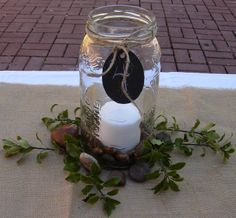 DR Ideas: Table with Pickle Jar centerpiece with candle and acorns in the middle with greens and rocks around it. Table number on construction paper with chalk tied on with jute twine.