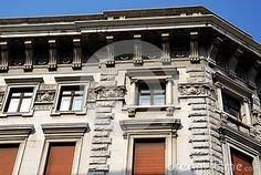 Photo taken at a palace in Trieste in Friuli Venezia Giulia (Italy). In the picture we see a high portion of the front and side of a building with architectural elements rather marked. Above the pitch of the roof we see the blue sky.