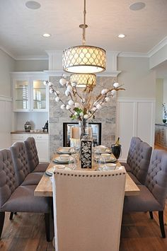 Dining Room decor ideas - Elegant traditional style dining room with passthrough stone clad fireplace, built in dry bar, double drum pendant lighting and upholstered grey chairs.