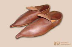 Schnabelschuh mit einem kleinen Schnabel. Die Form der Spitze basiert auf Sohlenfunden aus dem englischen Fund von Baynards Castle des späten 14. Jhdt. Das Oberleder ist an die deutschen Schnabelschuhe angepasst. Sohlenform enstammt dem Buch Shoes and Pattens, S. 30.