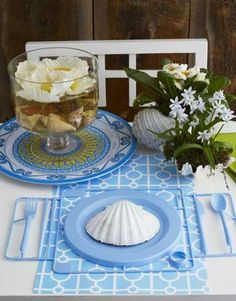 Ocean-Themed Table Setting    Use plastic plates and utensils for a casual sea-theme party. Seashells function as flower vases, decorative centerpieces, and place-setting embellishments.