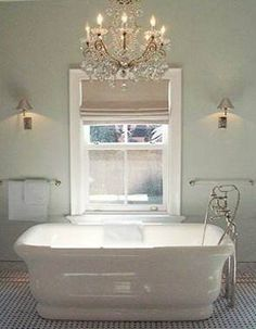 soft turquoise with a chandelier framing the tub