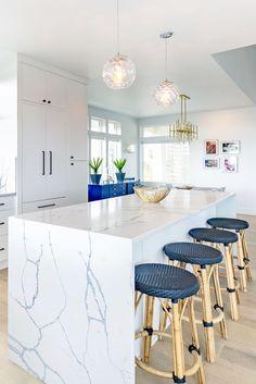 Kitchen with waterfall countertop. Daltile Statuary quartz. Light oak floor. Beach house, Port Aransas, Texas.