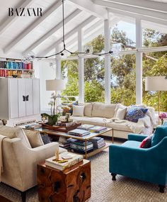 Kerr's living area has a neutral color palette, with bursts of teal and aquamarine introduced via accent cushions and statement arm chairs. Brightly patterned pillows, made from Hermès scarves, give the space a unique touch | Inside Miranda Kerr's Feminine, Eco-Friendly Malibu Home via MyDomaine